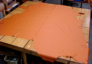 "A full cow hide, dyed orange. The table is marked in a 12"" x 12"" grid. Source: Brettunsvillage.com"