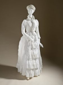 Dress circa 1885 featuring lots of cotton needle lace embellishment. Source: LA County Museum.