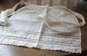Antique nainsook apron with lace trim. Source: Etsy.